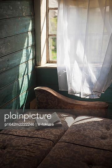 Ein Buch auf einem Sofa am Fenster - p1642m2222246 von V-fokuse