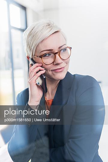 Portrait of confident businesswoman on cell phone in office - p300m1581650 von Uwe Umstätter