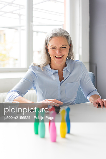 Laughing mature businesswoman playing with pins on desk in office - p300m2156529 by Robijn Page