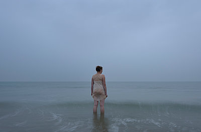 Woman in the sea, at dusk - p1132m925528 by Mischa Keijser