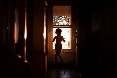 A Silhouette  Of A Small Boy In Front Of A Door - p1166m2094782 by Cavan Images
