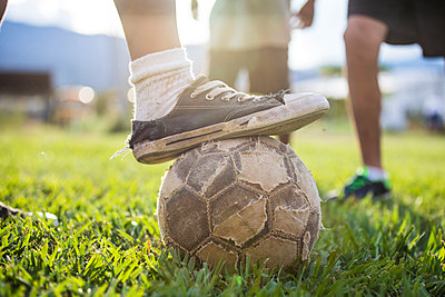 Soccer (football) player places old shoe on torn soccer ball. - p1166m2171566 by Cavan Images