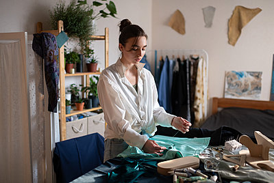 Concentrated designer working in home studio - p1166m2218558 by Cavan Images