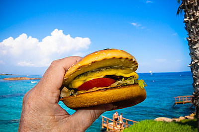 Hand holding cheeseburger by the sea - p1418m1541114 by Jan Håkan Dahlström
