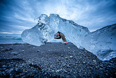 Man exploring ice formations, Diamond beach, Iceland - p429m2145599 by Romona Robbins Photography