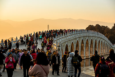 """""""Tourists over the 17 Arch Bridge at sunset, The Summer Palace; Beijing, China"""" - p442m2016247 by Dosfotos"""