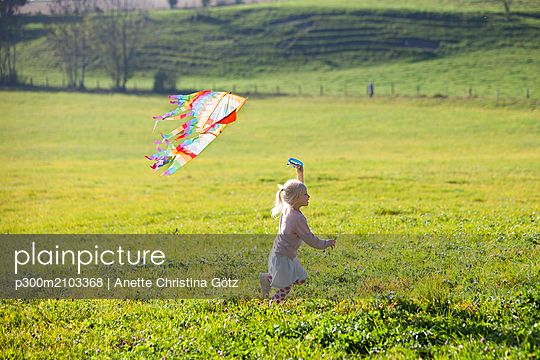 Little girl running in field with kite - p300m2103368 by Anette Christina Götz