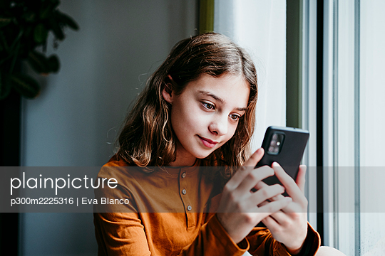 Pre-adolescent child using mobile phone while sitting by window at home - p300m2225316 by Eva Blanco