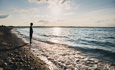 Full length of silhouette boy standing on shore at beach against sky during sunset - p1166m2025357 by Cavan Images