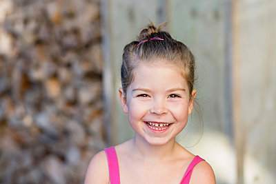 Close up portrait of young girl smiling at the camera - p1166m2201882 by Cavan Images