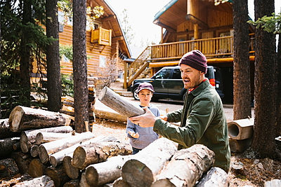 Father and son gathering firewood outside cabin - p1192m2094141 by Hero Images