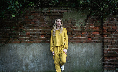 Blonde woman with curly hair and a yellow tracksuit - p1628m2260813 by Lorraine Fitch