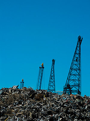 Cranes reaching over junkyard - p42916995 by Charlie Fawell