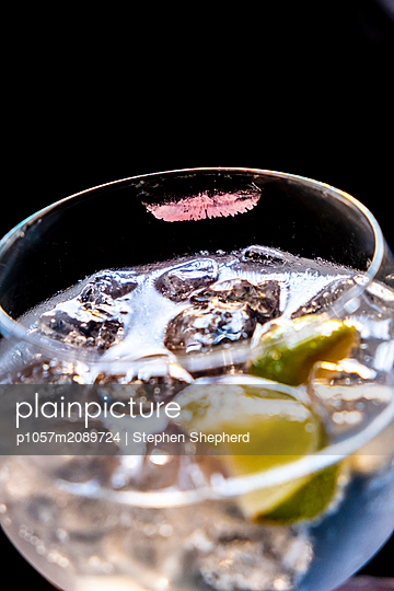 A large glass of Gin & tonic with a smudge of lipstick on the rim on a pub table. - p1057m2089724 by Stephen Shepherd