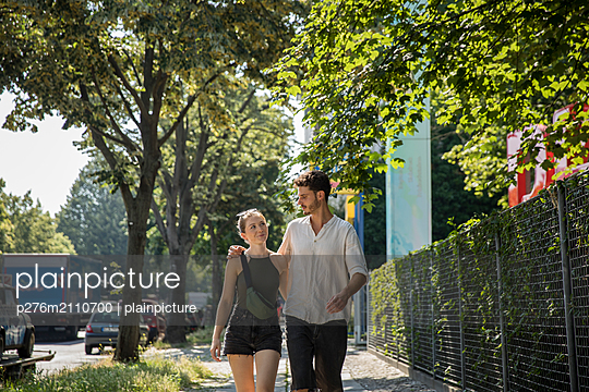 Young couple walking and in a conversation - p276m2110700 by plainpicture