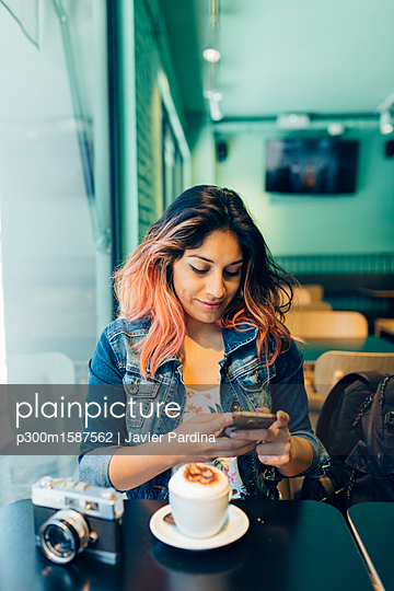 Smiling woman sitting in coffee shop looking at cell phone - p300m1587562 von Javier Pardina