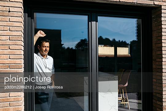 50-year-old man working at home, dining room and kitchen - p300m2286212 von Josep Rovirosa