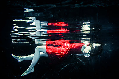 Woman in red dress floating underwater - p1019m1461903 by Stephen Carroll