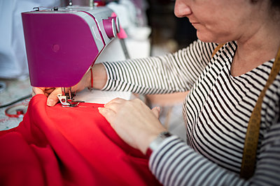 Closeup of adult woman seamstress sews clothes and put thread in needl - p1166m2131002 by Cavan Images