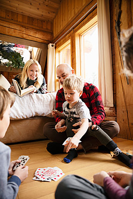 Family reading and playing cards in cabin - p1192m2094130 by Hero Images