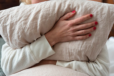 Woman holding pillow on bed - p1427m2084577 by Jamie Grill
