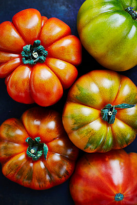 Five beef tomatos on black ground, elevated view - p300m929943f by Kai Schwabe