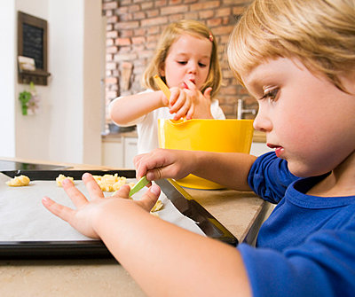 girl, boy preparing cookies for baking - p4298657f by Henglein & Steets