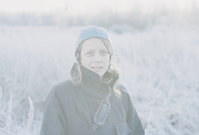 Young woman on frozen field  - p956m1515679 by Anna Quinn