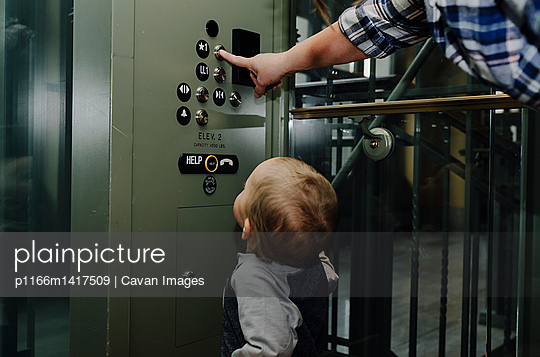 Son looking at mother pressing elevator button - p1166m1417509 by Cavan Images