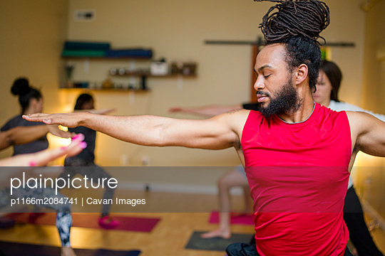 a handsome man practices yoga in a yoga class - p1166m2084741 by Cavan Images