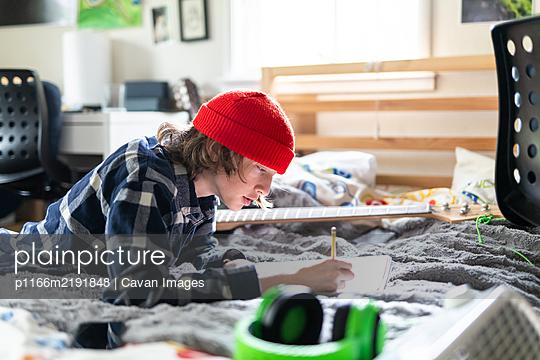 Teenage boy working on homework in bedroom surrounded by belongings - p1166m2191848 by Cavan Images