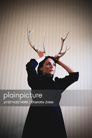 Woman with antlers on head, portrait - p1521m2214966 by Charlotte Zobel