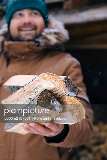 Man's hand holding firewood in winter, close-up - p300m2167381 by Konstantin Trubavin