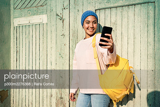 Smiling woman with backpack taking selfie through smart phone during sunny day - p300m2276368 by Rafa Cortés