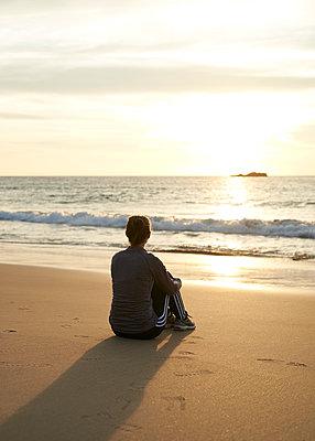 Frau sitzt am Strand  - p1124m1112580 von Willing-Holtz