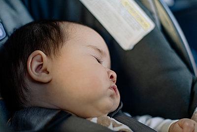 Baby sleeping in car seat - p1166m2078471 by Cavan Images
