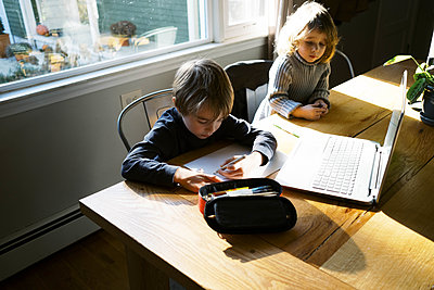kids in morning light sitting at table doing remote school - p1166m2232741 by Cavan Images