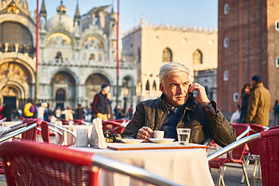 Man phoning in a sidewalk cafe on St. Mark's Square - p1312m2082202 by Axel Killian