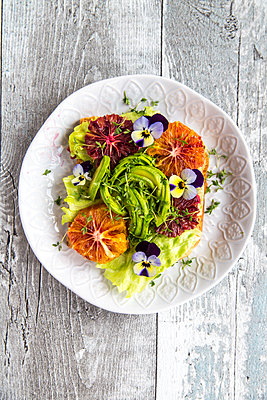 Toast garnished with iceberg salad, avocado, sliced blood orange, cress and horned violets - p300m1416677 by Sandra Roesch