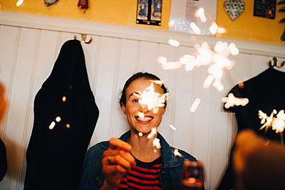 Cheerful young woman holding sparkler while enjoying dinner party at restaurant - p426m2046308 by Maskot
