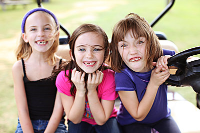 Caucasian girls making faces in golf cart - p555m1408730 by Shestock