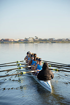 Female rowers rowing scull on sunny lake - p1023m1575842 by Richard Johnson