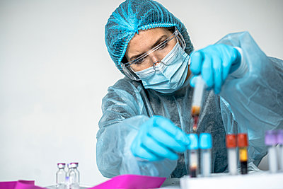 Blood test tube with label of Covid-19 also known as coronavirus or novel corona in scientist hand in laboratory. Female scientist is wearing highly protective suit, gloves, mask and glasses. - p1166m2235969 by Cavan Images