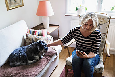 Senior woman using smart phone while stroking dog relaxing on sofa at home - p426m1114762f by Maskot