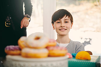 Portrait of smiling boy sitting by grandmother at dining table with donuts in foreground - p426m1580226 by Maskot
