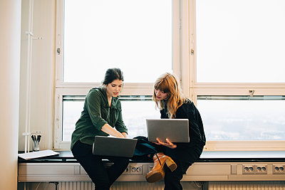 Confident female colleagues discussing over laptops while sitting on window sill at creative office - p426m1588462 by Maskot