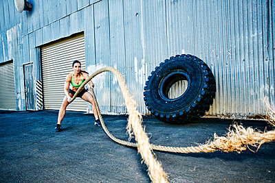 Mixed Race woman working out with heavy ropes outdoors - p555m1304129 by Peathegee Inc