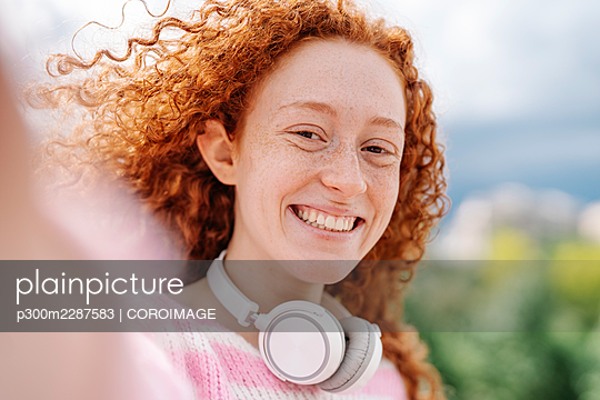 Cheerful young woman with curly hair wearing headphones - p300m2287583 by COROIMAGE