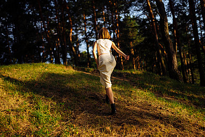 woman runs in the forest back view - p1166m2137035 by Cavan Images