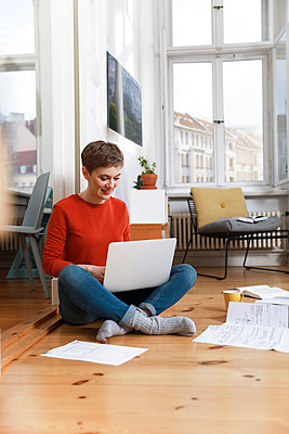 Woman sitting cross-legged on floor of her home, using laptop - p300m1588040 by Florian Küttler